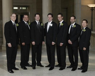 groom-and-groomsmen-wearing-black-suits-and-orchid-boutonnieres