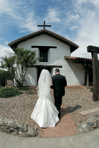 father-of-bride-walks-bride-to-the-entrance-of-mission-san-francisco-solano