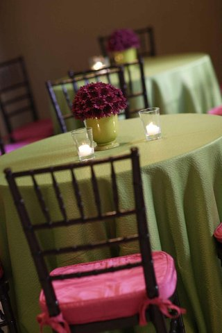cocktail-table-with-green-tablecloth-and-brown-chairs-with-pink-cushions