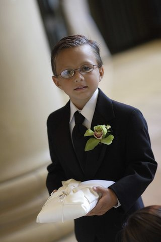 ring-bearer-wearing-green-orchid-boutonniere-and-carrying-white-pillow