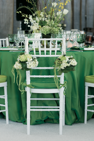 wedding-reception-chair-decorated-with-green-and-white-flowers-and-greenery