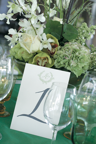 wedding-reception-table-with-hand-drawn-number-and-bouquet-of-green-and-white-flowers