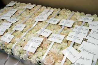 white-escort-card-under-ribbon-on-rose-bed