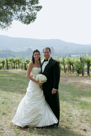 bride-in-a-pnina-tornai-gown-and-groom-in-a-black-tuxedo-at-kunde-estate-vineyards