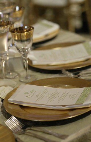 ivory-and-green-linens-with-gold-charger-and-gold-rimmed-glasses