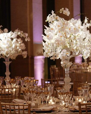 crystal-candelabra-with-white-orchids-on-top-on-table-with-gold-accented-place-settings