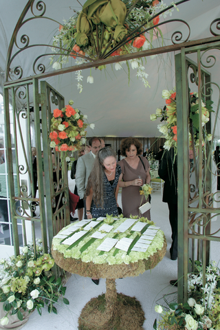 wedding-reception-place-card-table-is-covered-in-moss-and-topped-with-green-carnations