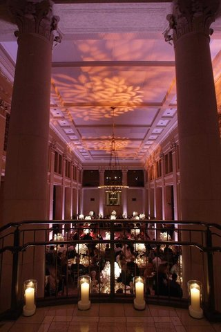 purple-and-pink-lighting-projections-on-ceiling-of-venue-with-columns-and-candlelight