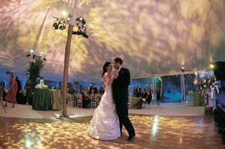 bride-in-a-pnina-tornai-gown-dances-with-a-groom-in-a-black-tuxedo