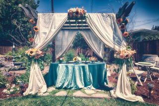 blue-table-under-canopy-of-white-drapes-with-sunflowers