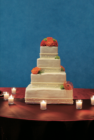 four-layer-white-cake-with-pearl-decorations-and-green-and-orange-flowers