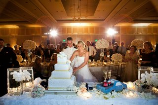 bride-and-groom-cut-wedding-cake-next-to-grooms-cake