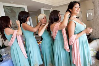 bridesmaids-in-blue-dresses-putting-on-matching-necklaces