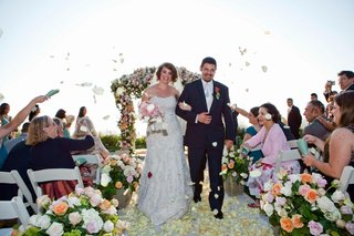 bride-and-groom-walk-up-aisle-with-rose-petal-toss