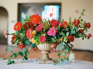wedding-ceremony-flower-arrangement-in-stone-urn-with-red-orange-pink-and-yellow-flowers