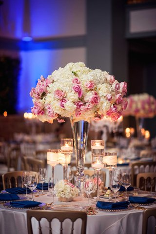 white-hydrangea-pink-rose-flower-arrangement-floating-candles-navy-blue-cobalt-napkins-gold-chairs