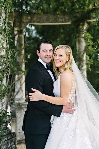 bride-in-angel-sanchez-illusion-back-wedding-dress-and-groom-in-tuxedo-gazebo-at-oheka-castle