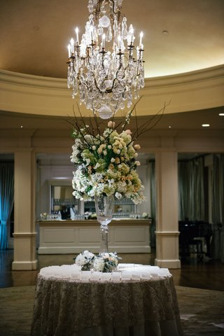 wedding-flowers-branches-ivory-blush-blooms-greenery-under-chandelier-wedding-reception-cocktail-hou