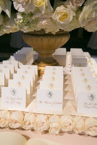 white-seating-cards-with-gold-calligraphy-on-white-roses