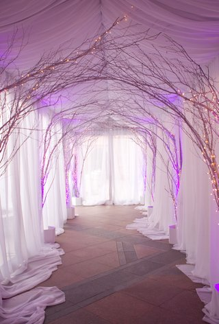 white-tent-and-string-lights-on-standing-branches