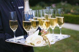champagne-in-flutes-with-white-roses-on-silver-tray-held-by-server