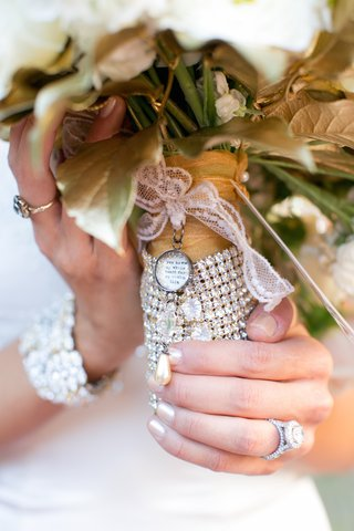 bride-holding-gold-dipped-bouquet-tied-with-lace
