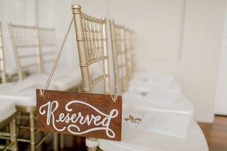wedding-ceremony-with-gold-chiavari-chairs-and-a-wood-reserved-sign