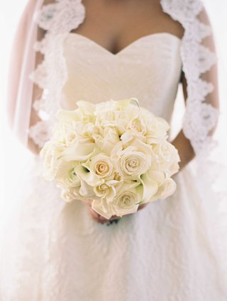 bride-with-lace-trim-veil-and-sweetheart-neckline-holding-white-rose-white-calla-lily-bouquet