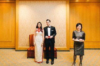 chinese-bride-in-a-white-qipao-with-gold-embroidery-and-red-trim-with-groom-in-black-tuxedo