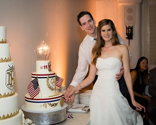 bride-and-groom-by-wedding-cakes-tall-white-gold-cake-and-groom-cake-with-american-flags-olympics