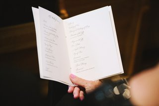 guest-holding-ceremony-booklet-while-sitting-in-pew