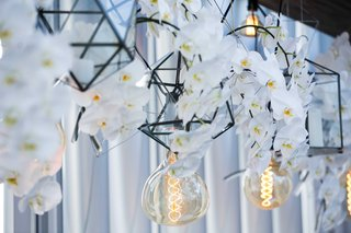 a-unique-display-for-hanging-light-bulbs-geometric-lanterns-and-cascading-white-orchids