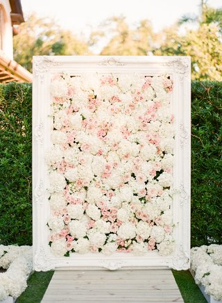 garden-wedding-ceremony-with-white-frame-filled-with-white-and-pink-flowers-at-the-altar