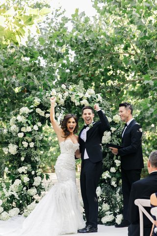 jillian-murray-and-dean-geyer-celebrating-their-wedding-day-after-ceremony-flower-arch-trees