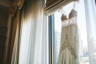 michal-medina-wedding-dress-from-dimitras-bridal-couture-hanging-in-window-chicago-wedding