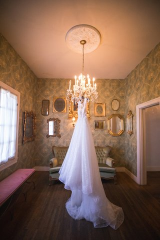 berta-wedding-dress-with-long-train-hanging-from-chandelier