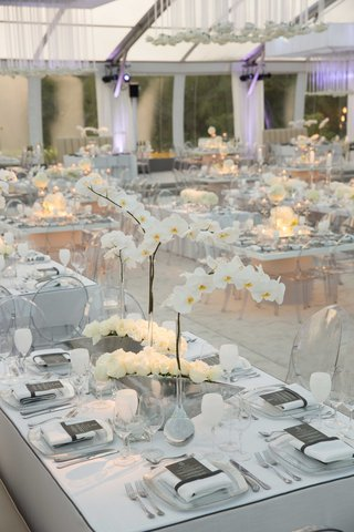 white-orchid-and-ivory-rose-centerpieces-in-silver-vases-white-goblets-tent-wedding-purple-lighting