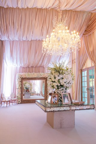 guest-book-table-under-chandelier-and-large-mirror