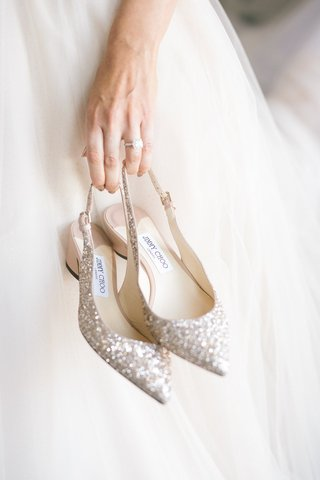 bride-in-wedding-dress-engagement-ring-holding-jimmy-choo-glitter-slingback-pumps-pointed-toe