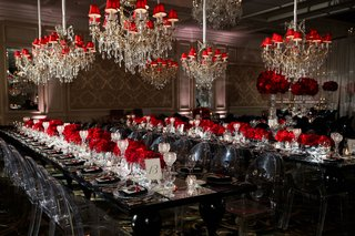 wedding-reception-long-black-table-clear-chairs-chandelier-red-shades-red-rose-flowers-crystal