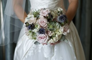 bride-holding-textured-flowers-in-white-wrap