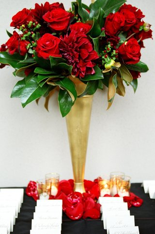 gold-trumpet-vase-filled-with-red-flowers