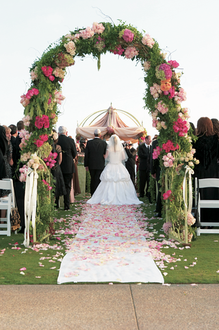 arch-at-beginning-of-aisle-of-greenery-and-pink-flowers