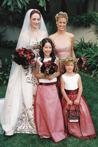 bride-and-bridesmaid-with-two-young-flower-girls-in-red-dresses