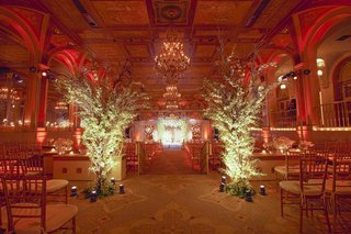 the-terrace-room-of-the-plaza-hotel-with-two-tall-arrangements-at-the-beginning-of-aisle