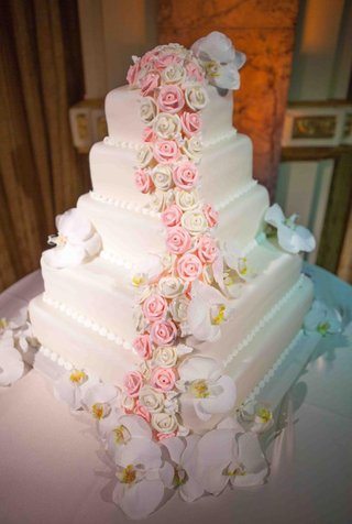 white-wedding-cake-with-square-layers-decorated-with-pink-and-white-sugar-roses-and-fresh-orchids