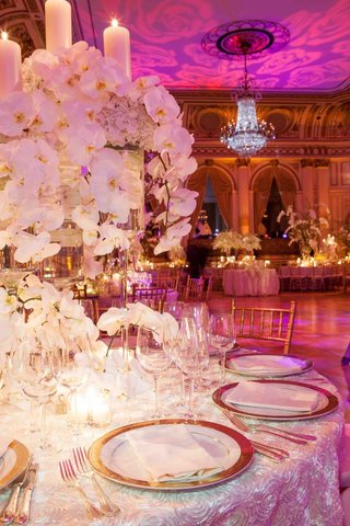 wedding-reception-table-with-gold-rimmed-chargers-and-white-orchid-arrangements