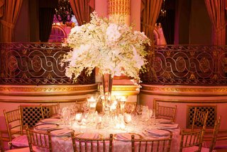 wedding-reception-centerpiece-of-white-orchids-surrounded-by-vases-with-floating-candles