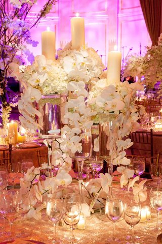 wedding-reception-table-with-arrangements-of-white-flowers-and-pillar-candles