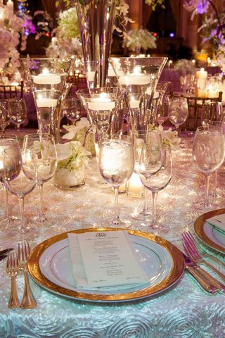 wedding-reception-table-with-floating-candles-and-small-arrangements-of-white-orchids